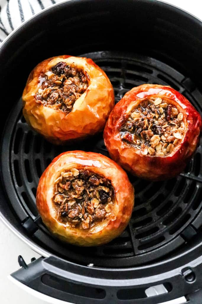 Baked whole apples filled in the center with crumble in a black air fryer basket