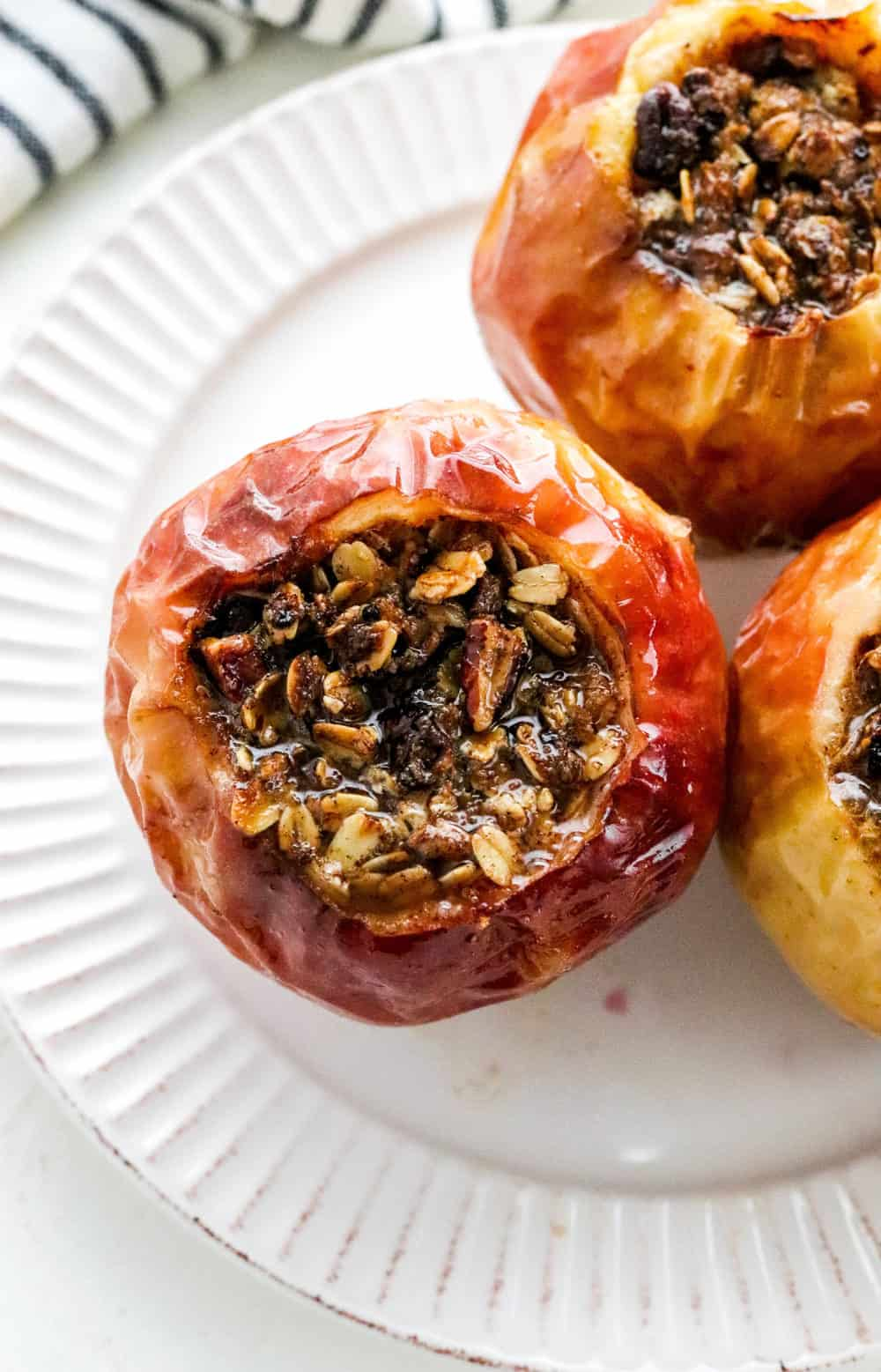 Baked whole red apple filled with an oat and pecan crumble that is golden brown with more filled baked apples next to it on a round white plate on a white counter.