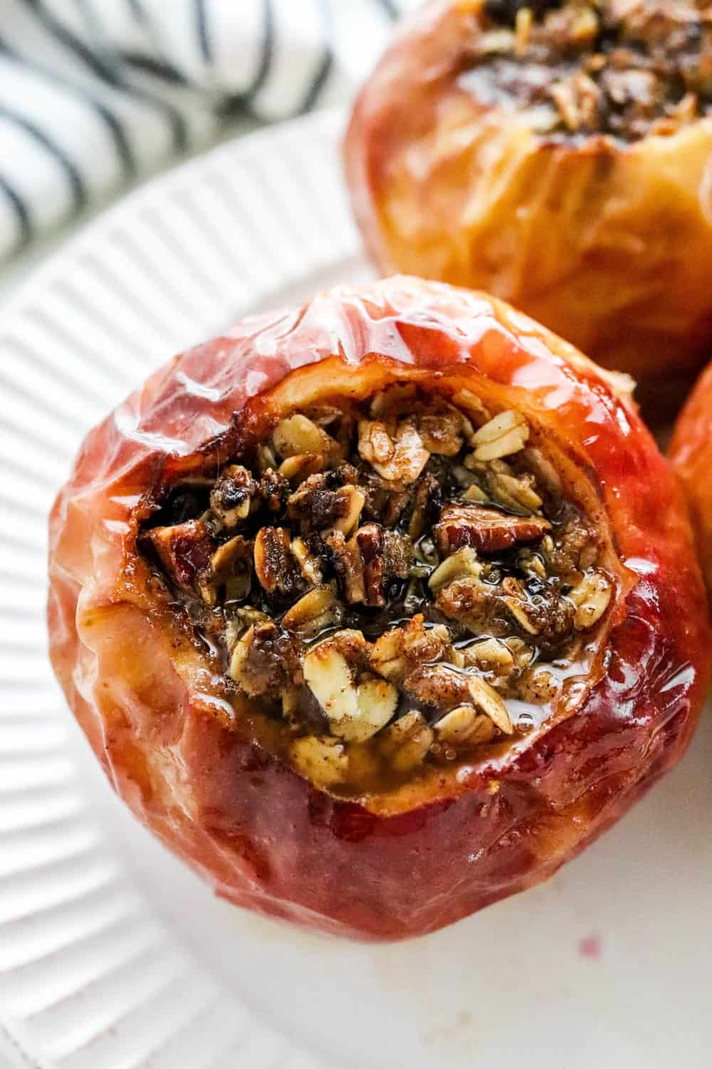 Whole baked apple filled with golden brown oat and nut crumble on a white plate with another baked able next to it and a blue and white striped towel behind it.
