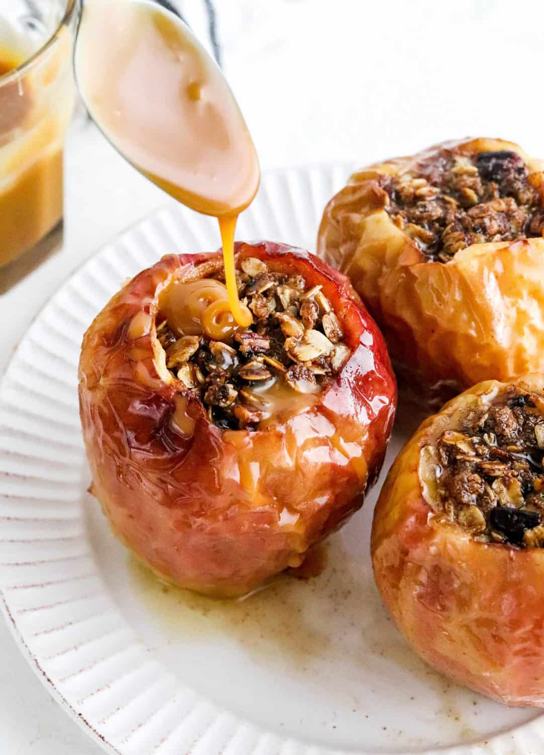 Spoon dripping caramel sauce onto a red soft filled baked apple with two more baked apples next to it on a round white plate and a jar of caramel sauce behind it.