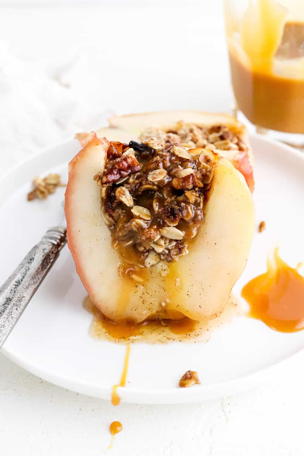 Sliced baked apples with gooey oat crumbs filling in the center on a white plate with a silver fork next to it and a jar of caramel sauce behind it.