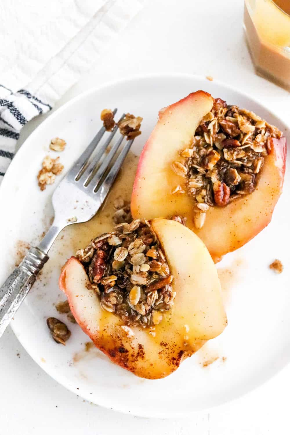 Sliced baked apples filled with oat and nut filling with a fork next to them on a round white plate.
